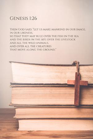 genesis: Genesis 1:26 Vintage tone of wooden cross on book background