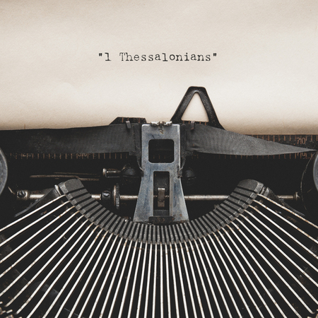 baptized: Word of  1 Thessalonians  on Antique typewriter with aged textured paper sheet.