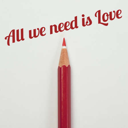 trait: Red pencil and a red heart with all we need is love word Stock Photo