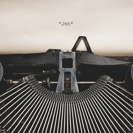 Word of  Job  on Antique typewriter with aged textured paper sheet. Imagens
