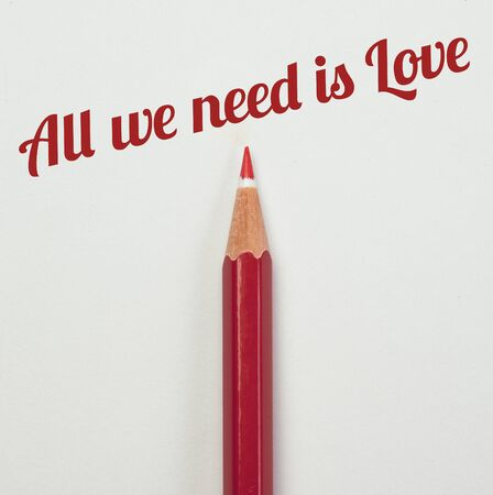 red pencil: Red pencil and a red heart with all we need is love word Stock Photo