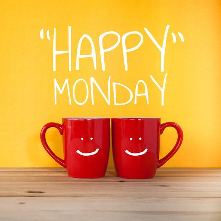 Glückliches Montagwort. Zwei Tassen Kaffee und stehen zusammen, um Herzform auf gelbem Hintergrund mit Lächelngesicht auf Tasse zu sein.