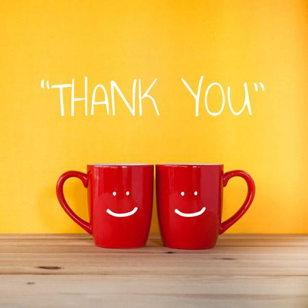 Merci mot.Two tasses de café et se tenir ensemble pour être en forme de coeur sur fond jaune avec sourire visage sur la tasse.