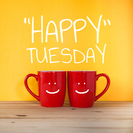 Happy Tuesday word.Two cups of coffee and stand together to be heart shape on yellow background with smile face on cup. 스톡 콘텐츠