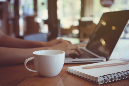Vintage style work office desk with a cup of coffee computer lap 스톡 콘텐츠