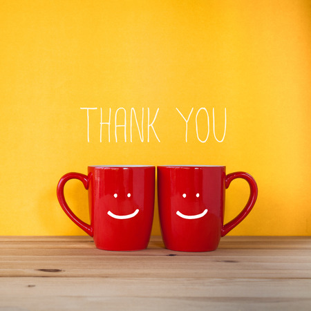 Thank You word with 2 red cups on yellow wall Archivio Fotografico