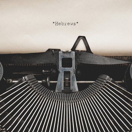 hebrews: Word of  Hebrews  on Antique typewriter with aged textured paper sheet.
