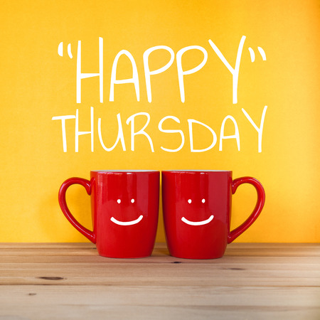thursday: Happy thursday word.Two cups of coffee and stand together to be heart shape on yellow background with smile face on cup.