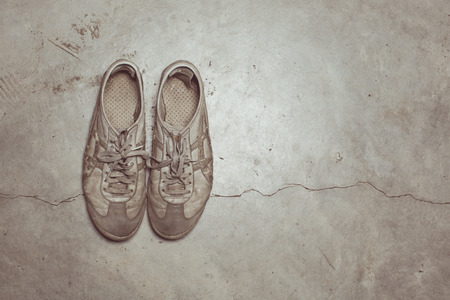 vintage tone of Dirty old shoes on concrete floor