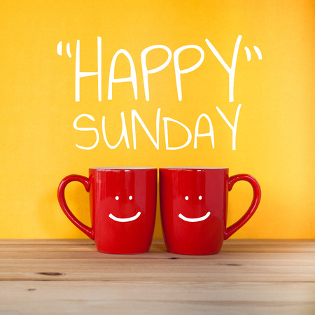 Happy sunday word.Two cups of coffee and stand together to be heart shape on yellow background with smile face on cup.