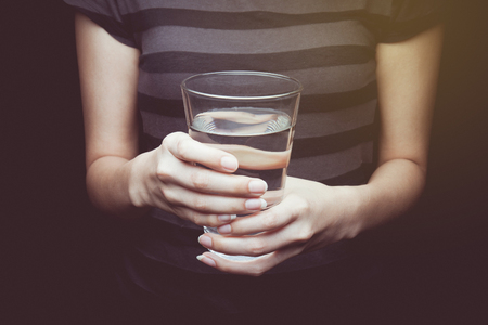 thumb keys: Vintage tone of Woman holds a glass of water. Give a glass of water. Drink more water. Black background. Stock Photo