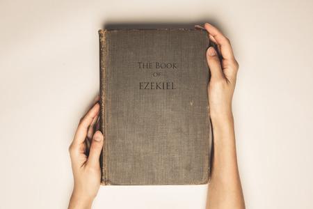spiritualism: Vintage tone of hands hold the book bible of ezekiel