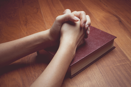 vintage tone of Woman hands praying with a bible