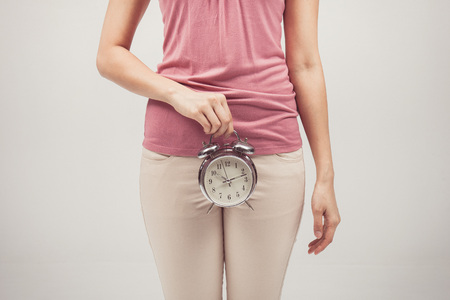 cystitis: Vintage tone of alarm clock in hands of woman Stock Photo