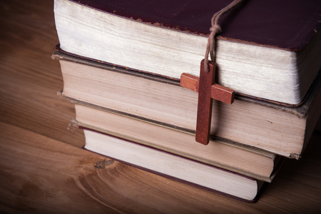 baptized: Closeup of wooden Christian cross necklace next to holy Bible