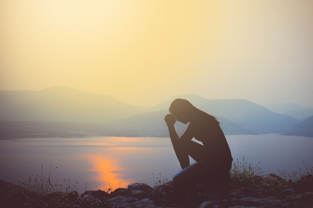meditation help: Silhouette of woman praying over beautiful sky background