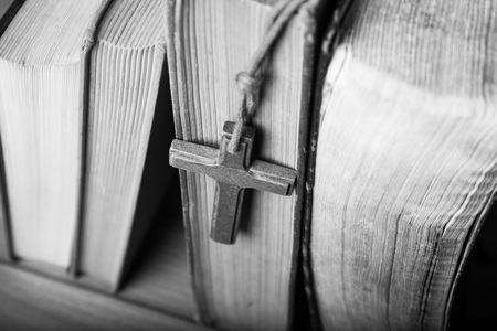 hymn: Closeup of wooden Christian cross necklace next to holy Bible