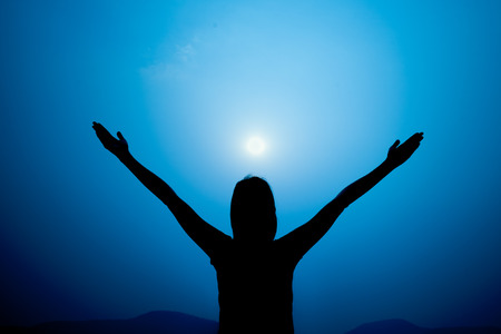 upraised: Silhouette of woman on a summit with upraised arms on the top mountain, Praise for GOD.