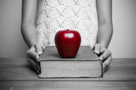 able to learn: A close-up of a christian woman reading the bible with red apple.