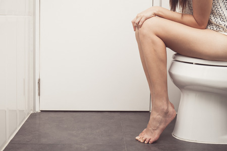 constipated: vintage tone of asian woman is sitting on the toilet. Stock Photo