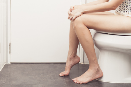 constipated: vintage tone of Hand of woman in bath towel sitting on toilet bowl Stock Photo