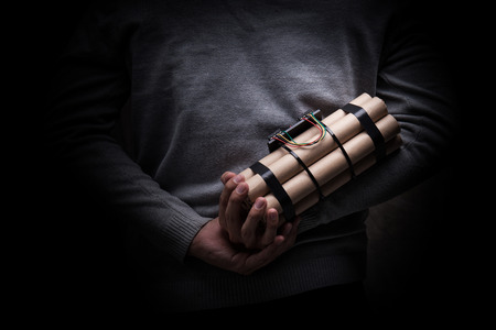 strapped: man in a black jacket strapped with explosives and detonator holds in hand Stock Photo
