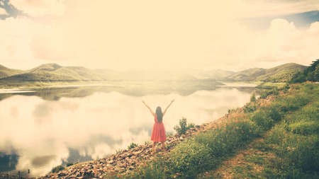 upraised: vintage tone of woman on a summit with upraised arms on the top mountain with the sunset, Praise for GOD.
