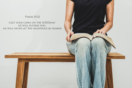 Casual young woman holds an open Bible Psalm 55:22 on her lap. Stock Photo