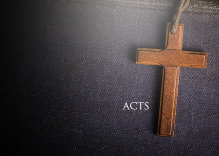 A cross with Bible book of acts Imagens