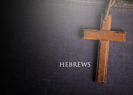 hebrews: A cross with Bible book of Hebrews Stock Photo