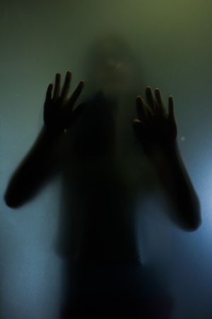 Trapped woman concept with back silhouette of hands behind matte glass