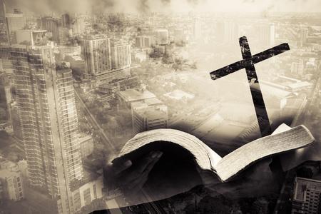 medios mixtos de la cruz y la biblia de la ciudad y de la mano sostienen