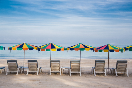 Quite beach with umbrellas and beach chairs and clear blue sky.
