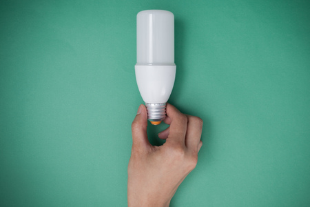 Hand holding LED Bulb with Lighting on green sky background. Eco power concept. Banco de Imagens