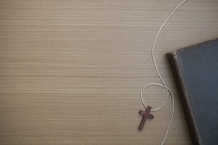 Cross with Bible, wooden christian cross and bible on the old wooden background. Banco de Imagens