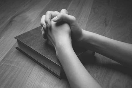 Hands on Bible with wooden background. Stockfoto