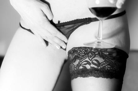 セクシーな女の子のソックスを身に着けているワインのガラスを保持しています。 写真素材