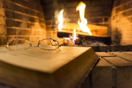 open book with glasses on it beside fireplace