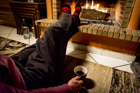 woman is warming in a fireplace while she is drinking coffee