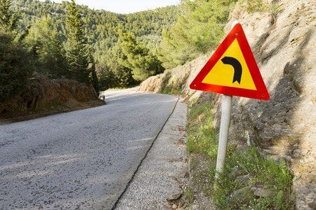 warning sign for dangerous left turn in the mountain 스톡 콘텐츠