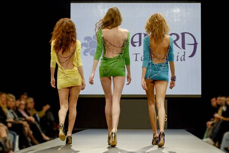 three sexy models catwalking on a fashion show