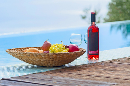 healthy bowl of fruits and bottle of wine in poolside