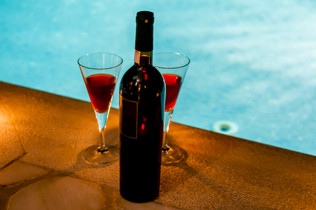 2 glasses and bottle of wine at poolside, romance Stock Photo