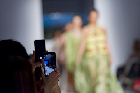 people from audience filming the fashion show with mobile phone