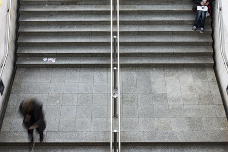 beggar siting on stairs in metro station in Athens