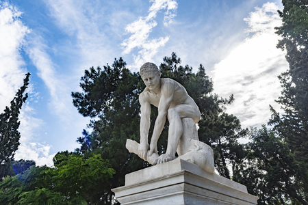 young male statue while trys to break a piece of wood