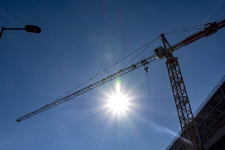 Construction crane on blue sky with sunny background
