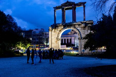 Tourists taking photos in front of hadrian gate in Athens on a winter cloudy blue hour day