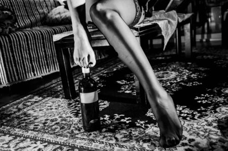 legs of sexy girl sitting on a table with her feet on a bottle of wine