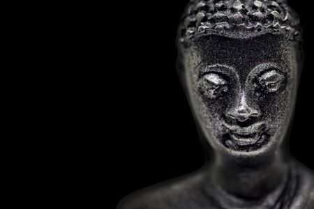 Face of buddha figurine from black stone isolated